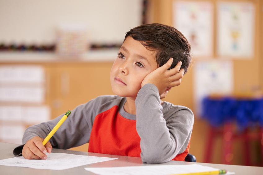 Portrait of a boy daydreaming in an elementary school class